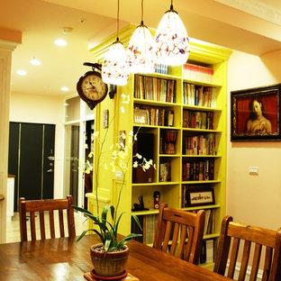 Idée de décoration pour une petite salle à manger ouverte sur la cuisine chalet avec un mur orange, sol en stratifié, aucune cheminée et un sol jaune.