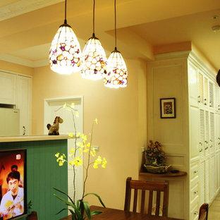 Ispirazione per una piccola sala da pranzo aperta verso la cucina rustica con pareti arancioni, pavimento in laminato, nessun camino e pavimento giallo