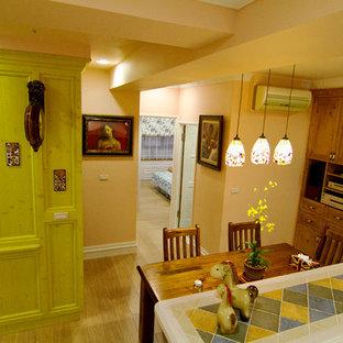 Esempio di una piccola sala da pranzo aperta verso la cucina rustica con pareti arancioni, pavimento in laminato, nessun camino e pavimento giallo