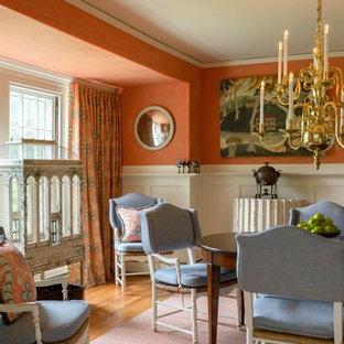 Réalisation d'une salle à manger ouverte sur la cuisine tradition de taille moyenne avec un mur orange et un sol en bois brun.