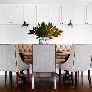 This is an example of a beach style kitchen/dining combo in Sydney with white walls, dark hardwood floors and brown floor.