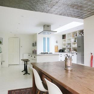 Idées déco pour une salle à manger ouverte sur la cuisine éclectique avec un mur blanc, un sol en bois peint et un sol blanc.