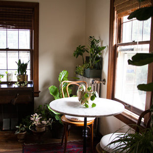 Small eclectic medium tone wood floor enclosed dining room photo in Seattle with white walls