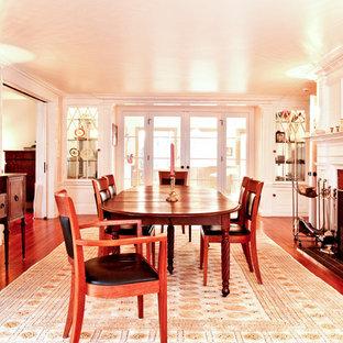 На фото: столовая в классическом стиле с белыми стенами, темным паркетным полом и фасадом камина из кирпича с