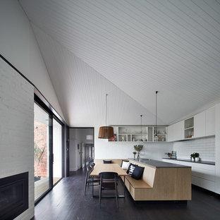 Foto på ett funkis kök med matplats, med vita väggar, mörkt trägolv, en standard öppen spis och en spiselkrans i tegelsten