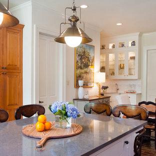 Modelo de comedor de cocina tradicional renovado, de tamaño medio, con paredes beige y suelo de ladrillo
