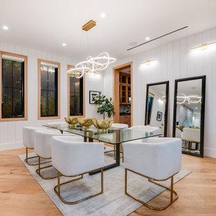 Immagine di una sala da pranzo country con pareti bianche, pavimento in legno massello medio, pavimento marrone e pareti in perlinato