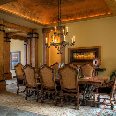 Example of a large mountain style dark wood floor enclosed dining room design in Other with beige walls