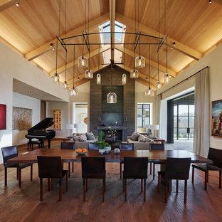 Diseño de comedor rural, abierto, con paredes beige, suelo de madera en tonos medios, chimenea tradicional, marco de chimenea de hormigón y suelo marrón