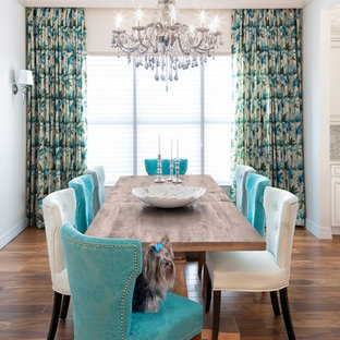 Mid-sized elegant medium tone wood floor and brown floor kitchen/dining room combo photo in Miami with white walls and no fireplace