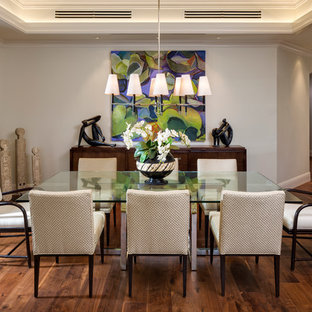 Idées déco pour une salle à manger ouverte sur le salon exotique avec un mur gris et un sol en bois foncé.