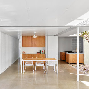 This is an example of a mid-sized contemporary dining room in Sydney with white walls and concrete floors.