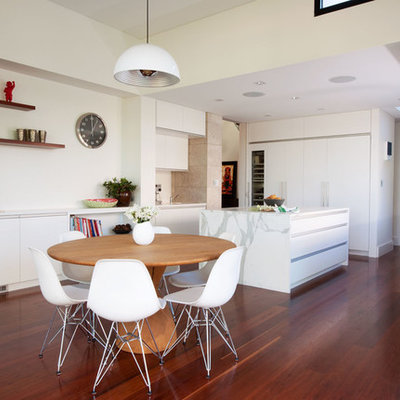 Example of a trendy dark wood floor kitchen/dining room combo design in Sydney with white walls
