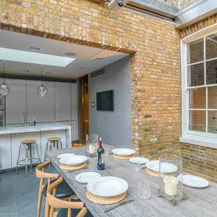 Large contemporary open plan dining room in London with yellow walls, limestone flooring and grey floors.