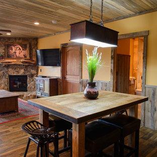 Свежая идея для дизайна: кухня-столовая с желтыми стенами, темным паркетным полом, угловым камином и фасадом камина из камня - отличное фото интерьера