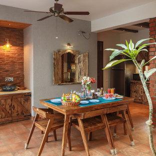 На фото: столовая в восточном стиле с разноцветными стенами, кирпичным полом и коричневым полом с