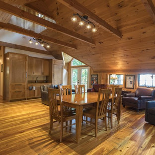 Example of a mid-sized mountain style medium tone wood floor and brown floor great room design in Other with red walls and no fireplace