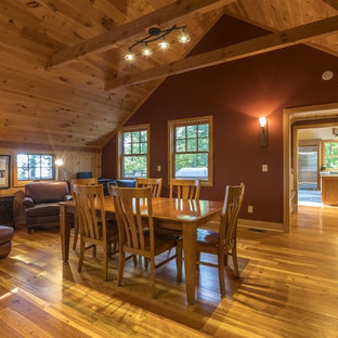 Great room - mid-sized rustic medium tone wood floor and brown floor great room idea in Other with red walls and no fireplace