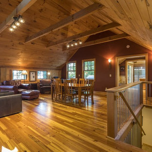 Mid-sized mountain style medium tone wood floor and brown floor great room photo in Other with red walls and no fireplace
