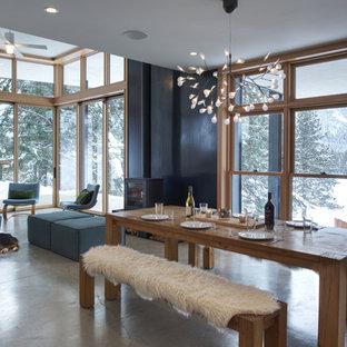 Modern inredning av en mellanstor matplats med öppen planlösning, med vita väggar, betonggolv, en öppen vedspis, en spiselkrans i metall och grått golv