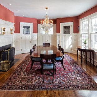 Идея дизайна: огромная отдельная столовая в классическом стиле с красными стенами, паркетным полом среднего тона, стандартным камином и фасадом камина из дерева