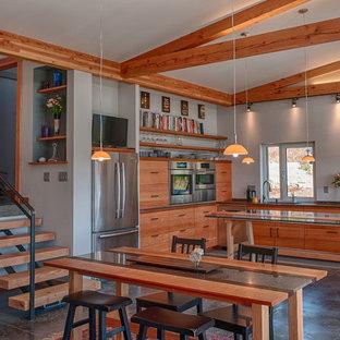 Foto di una sala da pranzo aperta verso il soggiorno design di medie dimensioni con pareti grigie, pavimento in cemento e nessun camino