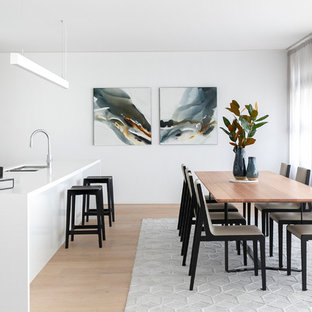 Inspiration for a contemporary kitchen/dining combo in Sydney with white walls, medium hardwood floors, no fireplace and brown floor.