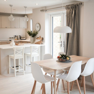 This is an example of a scandinavian dining room in Hampshire with white walls, light hardwood flooring and beige floors.