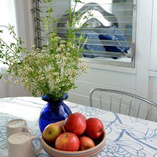 Ispirazione per una piccola sala da pranzo country con pareti bianche, pavimento in vinile e pavimento marrone