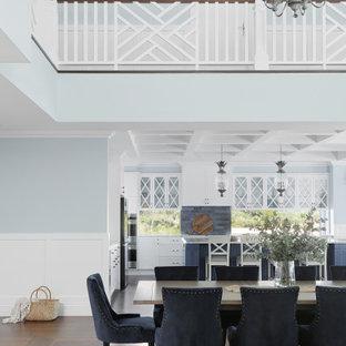 На фото: огромная гостиная-столовая в морском стиле с разноцветными стенами, темным паркетным полом, коричневым полом, кессонным потолком и панелями на стенах с