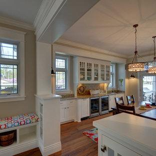Modelo de comedor de estilo americano, grande, abierto, con paredes beige y suelo de madera en tonos medios
