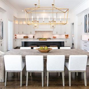 Immagine di una grande sala da pranzo aperta verso la cucina tradizionale con parquet scuro, pareti bianche, nessun camino e pavimento marrone