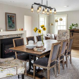 Immagine di una grande sala da pranzo chic chiusa con pareti grigie, parquet chiaro, camino classico, cornice del camino piastrellata e pavimento beige