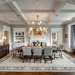 Example of a classic medium tone wood floor enclosed dining room design in New York with gray walls, a standard fireplace and a wood fireplace surround
