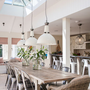 This is an example of a large beach style open plan dining room in Sussex with light hardwood flooring.