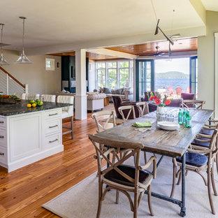 Esempio di una grande sala da pranzo aperta verso il soggiorno american style con pareti grigie, pavimento in legno massello medio e pavimento marrone