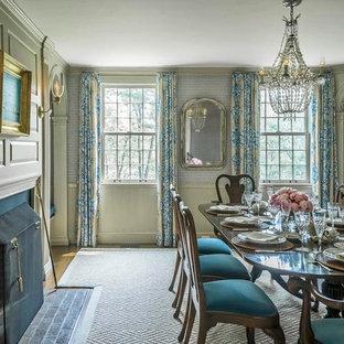 Immagine di una grande sala da pranzo aperta verso la cucina vittoriana con pareti grigie, parquet scuro, camino classico e cornice del camino in legno
