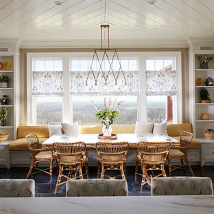 Mittelgroße Landhausstil Wohnküche mit beiger Wandfarbe, schwarzem Boden und Kalkstein in New York