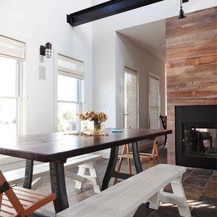 Diseño de comedor de cocina contemporáneo, pequeño, con paredes blancas, suelo de pizarra, chimenea de doble cara, marco de chimenea de madera y suelo multicolor