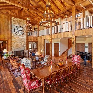 Ejemplo de comedor rural, grande, abierto, con paredes marrones, suelo de madera en tonos medios, chimenea tradicional y marco de chimenea de piedra