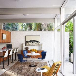 Idées déco pour une grand salle à manger ouverte sur la cuisine contemporaine avec un mur blanc, un sol gris et un mur en parement de brique.