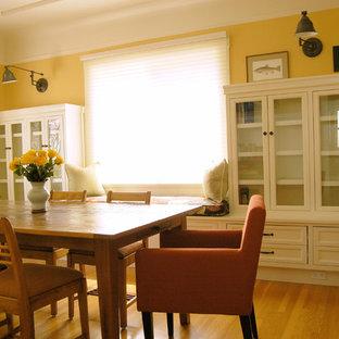 Immagine di una sala da pranzo classica di medie dimensioni e chiusa con pareti gialle e pavimento in legno massello medio