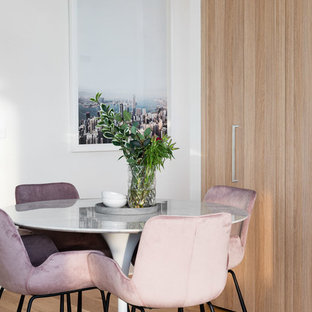 Contemporary dining room in Melbourne with white walls, medium hardwood floors and brown floor.