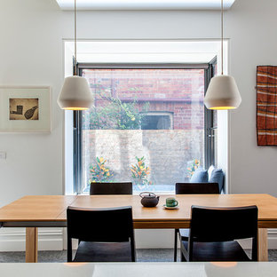 This is an example of a mid-sized contemporary open plan dining in Melbourne with white walls and grey floor.