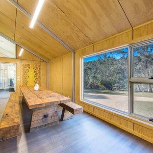 Immagine di una sala da pranzo aperta verso la cucina industriale di medie dimensioni con pareti marroni e pavimento in legno massello medio
