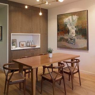 Imagen de comedor actual, pequeño, abierto, sin chimenea, con paredes blancas, suelo de madera en tonos medios y suelo marrón