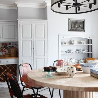 Inspiration for a medium sized farmhouse dining room in London with grey floors, grey walls and medium hardwood flooring.