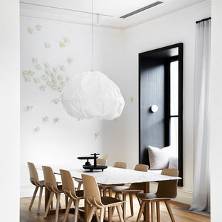 Inspiration for a scandinavian separate dining room in Melbourne with white walls, medium hardwood floors and brown floor.