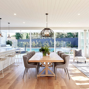 Design ideas for a contemporary open plan dining in Sydney with white walls, medium hardwood floors and brown floor.