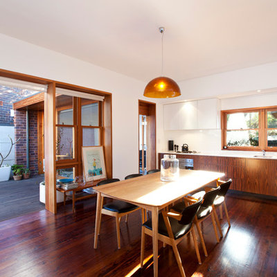 Trendy dark wood floor kitchen/dining room combo photo in Other with white walls